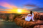 Couple in hug watching sunset on the edge of the cliff