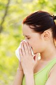 picture of hay fever  - Attractive woman outdoor with tissue having allergy - JPG
