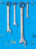 Kit Of Adjustable Grunge Metallic Screw Wrench With Dirty Blue Background