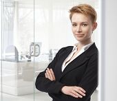 Young caucasian attractive businesswoman standing arms crossed at business office. Leaning against w