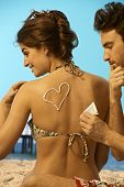 Caucasian man having fun putting sunscreen cream on back of attractive caucasian woman in swimsuit a