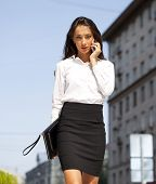 Young beautiful business woman talking on mobile phone