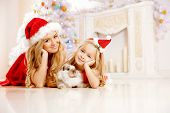 Mother and daughter dressed as Santa celebrate Christmas. Family at the Christmas tree. Woman and gi