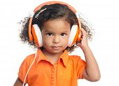 Lttle girl with an afro hairstyle enjoying her music on bright orange headphones (isolated on white)