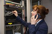 Pretty technician talking on phone while fixing server in large data center
