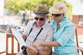 Happy tourist couple looking at map in the city on a sunny day