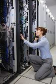 Serious technician talking on phone while analysing server in large data center