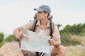 Portrait of a hiking man sitting with map on mountain terrain