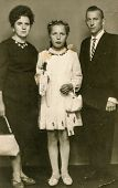 SIERADZ, POLAND - CIRCA 1960 - Vintage photo of parents with little girl at her First Communion.