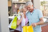 Happy mature couple looking at their shopping purchases on a sunny day