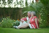 Elderly couple sitting on grass
