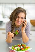 Happy Young Woman Eating Greek Salad In Kitchen And Talking Cell Phone