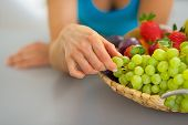 Closeup On Young Woman With Fruits Plate Eating Grape