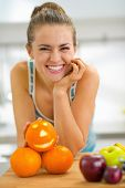 Portrait Of Happy Young Woman With Halloween Orange In Kitchen