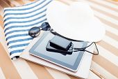 beach, summer vacations and technology concept - close up of tablet pc, notebook, smartphone and sum