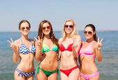 summer vacation, holidays, gesture, travel and people concept- group of smiling young women showing