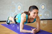 fitness, sport, training, future technology and lifestyle concept - smiling woman doing exercises on