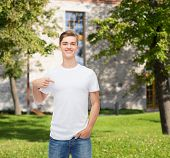 gesture, advertising, summer vacation, education and people concept - smiling young man in blank white t-shirt pointing finger on himself over campus background