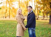love, relationship, family and people concept - smiling couple holding hands in autumn park