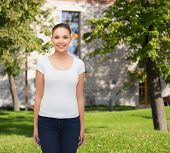 advertising, summer vacation, education and people concept - smiling young woman in blank white t-sh