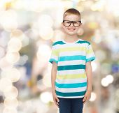 vision, education, holidays and school concept - smiling little boy in eyeglasses over sparkling bac