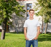 advertising, vacation, education and people concept - smiling young man in blank white t-shirt over