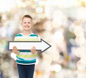 advertising, direction, holidays and childhood concept - smiling little boy with white blank arrow pointing right sparkling background