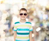 happiness, summer and people concept - smiling cute little boy in sunglasses over sparkling backgrou