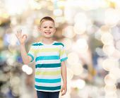 childhood, gesture, holidays and people concept - smiling little boy in casual clothes making OK gesture over sparkling background