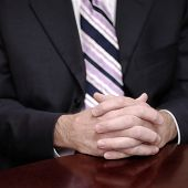 Business man sitting at table holding hands in office