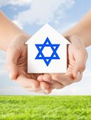 religion, judaism and charity concept - close up of woman hands holding house with star of david over blue sky with grass background