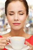 leisure, happiness, holidays and drink concept - smiling woman in red dress with closed eyes holding