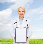 healthcare and medicine concept - smiling female doctor with stethoscope and clipboard and blank pag