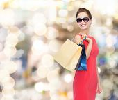 shopping, sale, gifts and holidays concept - smiling woman in red dress and sunglasses with shopping