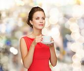 leisure, happiness, holidays and drink concept - smiling woman in red dress with cup of coffee over