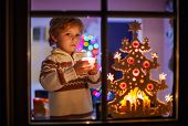 Happy Little Child Standing By Window At Christmas Time And Holding Candle