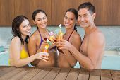 Portrait of cheerful young people toasting drinks in the swimming pool