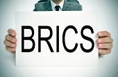 man wearing a suit holding a signboard with the word BRICS, for the five major emerging national eco