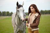 woman long hair kissing beautiful horse
