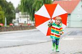 Beautiful Child With Red Umbrella And Colorful Jacket Outdoors At Rainy Day