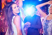 Joyful girls and guys dancing in night club