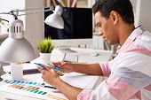Handsome businessman in casual looking at palette in office