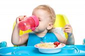 Little boy drinking water while sitting at table
