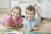 Portrait of happy siblings with story books lying on floor in living room