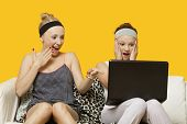Two shocked young women using laptop sitting on sofa against yellow background