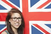 Portrait of cheerful young woman wearing eyeglasses against British flag