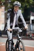 Portrait of young businessman riding bicycle