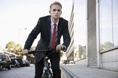 Handsome young businessman riding bicycle on street