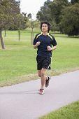Young Chinese man jogging at park
