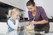 Girl looking at mother cooking in kitchen